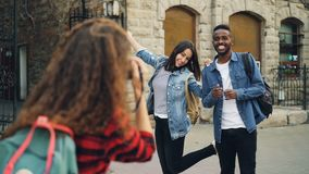 Kreatywnie dziewczyny i faceta przyjaciele pozują dla kamery pozyci w ulicie podczas gdy młoda kobieta z plecakiem bierze zdjęcie wideo