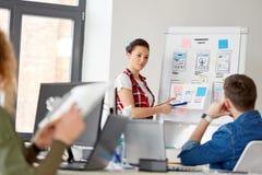 Kreatywnie kobieta pokazuje interfejs użytkownika przy biurem zdjęcia stock