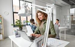 Kreatywnie kobieta z laptopem pracuje przy biurem zdjęcia royalty free