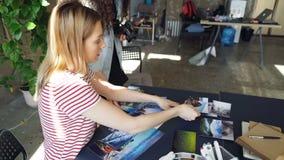 Kreatywnie koledzy umieszcza obrazki na stołu i strzelaniny mieszkaniu kłaść podczas gdy opowiadający o projektować projekt Odgór zdjęcie wideo