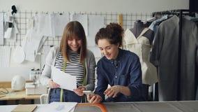 Kreatywnie krawcowe używają smartphone i patrzeją odzieży nakreślenia podczas gdy pracujący w ładnym studiu Atrapa, szy zbiory wideo