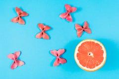 Kreatywnie lato układ robić grapefruitowy i barwiony makaron manny papillon na jaskrawym błękitnym tle Owocowy minimalny pojęcie obrazy royalty free