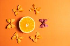 Kreatywnie lato układ robić pomarańcze i barwiący makaron manny papillon na jaskrawym pomarańczowym tle Owocowy minimalny pojęcie obraz stock