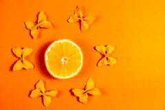 Kreatywnie lato układ robić pomarańcze i barwiący makaron manny papillon na jaskrawym pomarańczowym tle Owocowy minimalny pojęcie obrazy stock