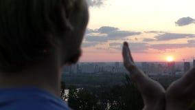 Kreatywnie mężczyzna utrzymuje słońce w jego rękach przy zmierzchem w Kyiv w mo zbiory wideo