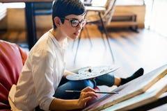 Kreatywnie młody żeński artysta maluje nowego obrazek zdjęcie royalty free