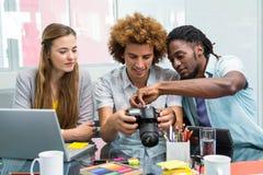 Kreatywnie młodzi ludzie biznesu patrzeje cyfrową kamerę Fotografia Royalty Free