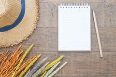 Kreatywnie mieszkanie nieatutowy pojęcie, Suszący kwiaty, słomiany kapelusz i puste miejsce notatnik z ołówkiem na drewnianym jes Obraz Royalty Free