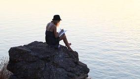 Kreatywnie osobowość z notatnikiem na brzeg rzeki podczas zmierzchu zbiory