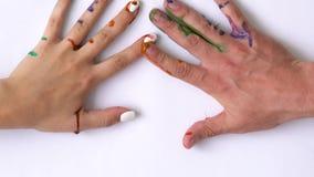 Kreatywnie pojęcie - mężczyzna i kobieta robimy drukom ich malować ręki na białym tle zdjęcie wideo