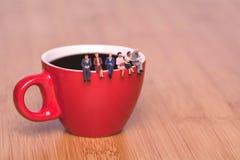 Kreatywnie pojęcie o pić kawę i czekać Miniaturowi ludzie na filiżance fotografia royalty free