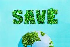Kreatywnie pojęcie z konturu literowania Save w zielonych świeżych traw flancach i część planeta modelujemy na błękitnym turkusow Zdjęcia Stock