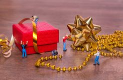 Kreatywnie pojęcie z miniaturowymi ludźmi i prezenta pudełkiem na woode zdjęcie royalty free