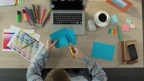 Kreatywnie praca fachowy projektant wnętrz, męski rozcięcie barwił papier zbiory
