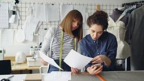 Kreatywnie projektanci mody oglądają nakreślenia pracować blisko szwalnego biurka Młode kobiety opowiadają i sprawdzają zbiory
