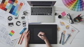 Kreatywnie projektant używa grafiki pastylkę przy jej stołem podczas gdy pracujący zbiory