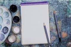 Kreatywnie przestrzeń Pracująca przestrzeń artysta na podławym stole: farba guasz, notatnik, ołówki zdjęcia royalty free