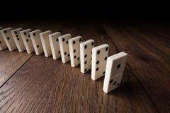 Kreatywnie tło, biały domino na brązu drewnianym tle, Pojęcie domino skutek, reakcja łańcuchowa zdjęcie royalty free