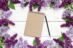 Kreatywnie układ robić z bzów kwiatami i pustym modnisia notatnikiem na białym drewnianym tle zdjęcie royalty free