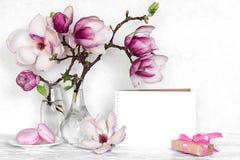 Kreatywnie układ robić z różowymi magnolia kwiatami, opróżnia kartę, macarons i prezenta pudełko na białym drewnianym tle, fotografia royalty free