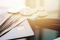 Kreditkarte, Geld, Münzen und Stift auf Schreibtischtabelle lizenzfreie stockfotos