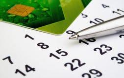 Kreditkarte mit einem Stift und Daten des Monats Stockbilder