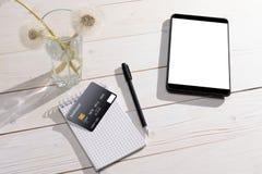 Kreditkarte, Tablette und Notizbuch mit Stift auf dem Tisch Lizenzfreie Stockfotografie