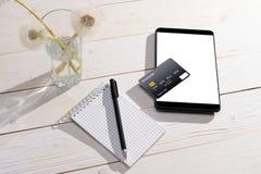 Kreditkarte, Tablette und Notizbuch mit Stift auf dem Tisch Stockbilder