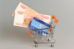 Kreditkarte und Geld innerhalb des Warenkorbes auf Grau Lizenzfreie Stockfotografie