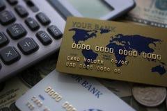Kreditkarte und Taschenrechner, die auf gro?er Menge US-Geld liegen lizenzfreie stockbilder
