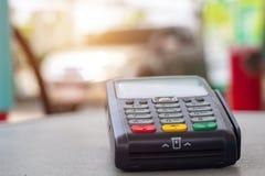 Kreditkartemaschine mit Brennstoffaufnahmetreibstoff des Autos an der Benzinstation im Hintergrund stockfotos