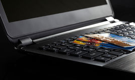 Kreditkarten auf einem Laptop Stockfotos