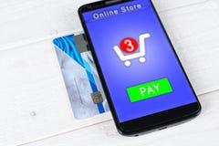 Kreditkarten und Smartphone, die auf einem Holztisch liegen Stockbilder