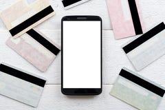 Kreditkarten und Smartphone, die auf einem Holztisch liegen Lizenzfreies Stockbild