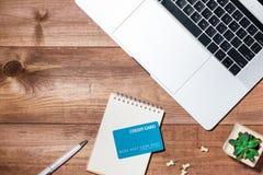 Kreditkort-, bärbar dator-, smartphone- och kaffekopp på trätabellen Arkivbild