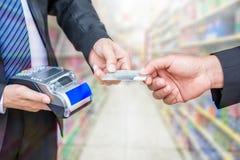 Kreditkort för handinnehavlön med affärsmannen som använder betalninguttryck Arkivbild