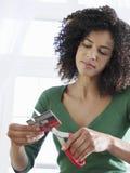 Kreditkort för kvinna för blandat lopp bitande Arkivfoto