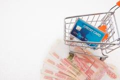 Kreditkort i shoppingspårvagnanseendet på rysspengar på vit bakgrund med kopieringsutrymme arkivfoto