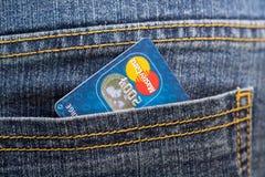 Kreditkort Mastercard i bakfickan av jeans Arkivbild