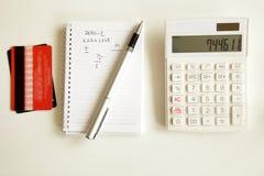 Kreditkort med räknemaskinen på tabellen Arkivfoton