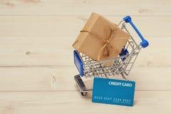 Kreditkort och shoppingvagn med gåvaasken som slås in med papper kraft på tabellen royaltyfri foto