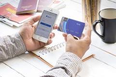 Kreditkort och Smartphone Augusti 1, hållande craditkort för man och smartphone och öppen paypal plats för betalning som är onlin arkivfoton