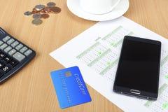 Kreditkort på ett skrivbord med en räknemaskin och en kalender royaltyfri bild