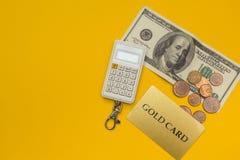 Kreditkort, räknemaskin och dollar på gul bakgrund royaltyfria bilder