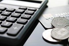 Kreditkort, räknemaskin och mynt på tabellen för kontorsskrivbord Arkivfoto
