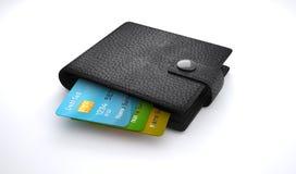 Kreditkortar i läderplånbok på vit bakgrund Arkivbild