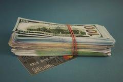 Kreditkortar och en packe av pengar på en vanlig blå bakgrund arkivfoto