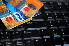 Kreditkortar på datortangentbordet med märkeslogoVISUMET och MASTERCARD Arkivbild