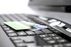 Kreditkortar på ett tangentbord Arkivfoton