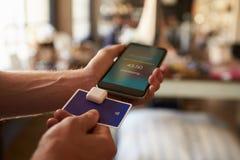 Kreditkortbetalning App som fästas till mobiltelefonen arkivbild
